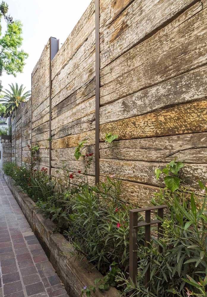 Fachada de muro em madeira rústica contornada por um lindo canteiro