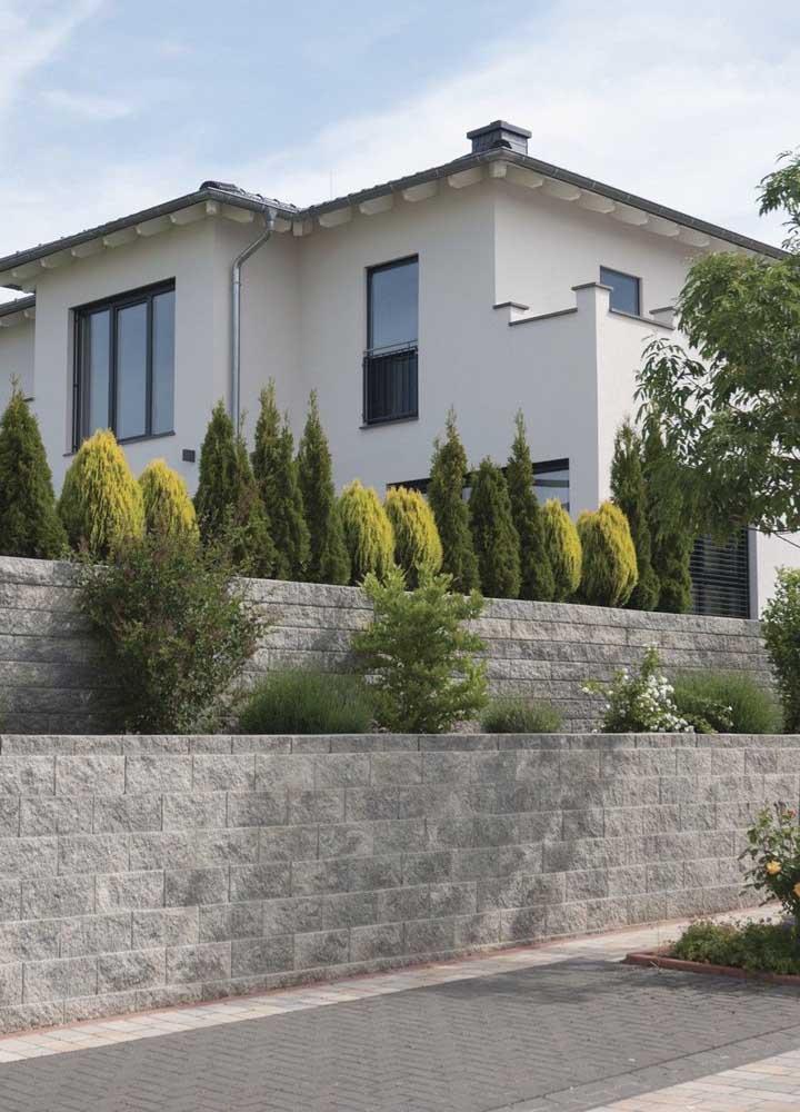 As pedras em tons de cinza usadas na fachada do muro trazem um toque clássico à residência