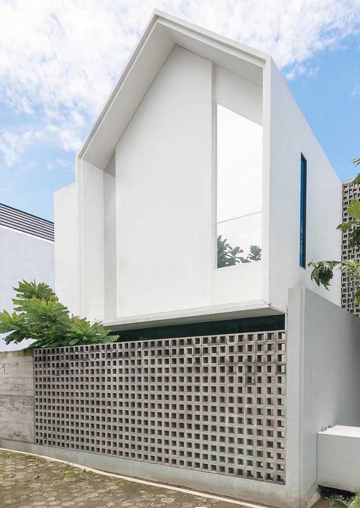 Fachada de muro em alvenaria com detalhes vazados para realçar a estética moderna e contemporânea da casa