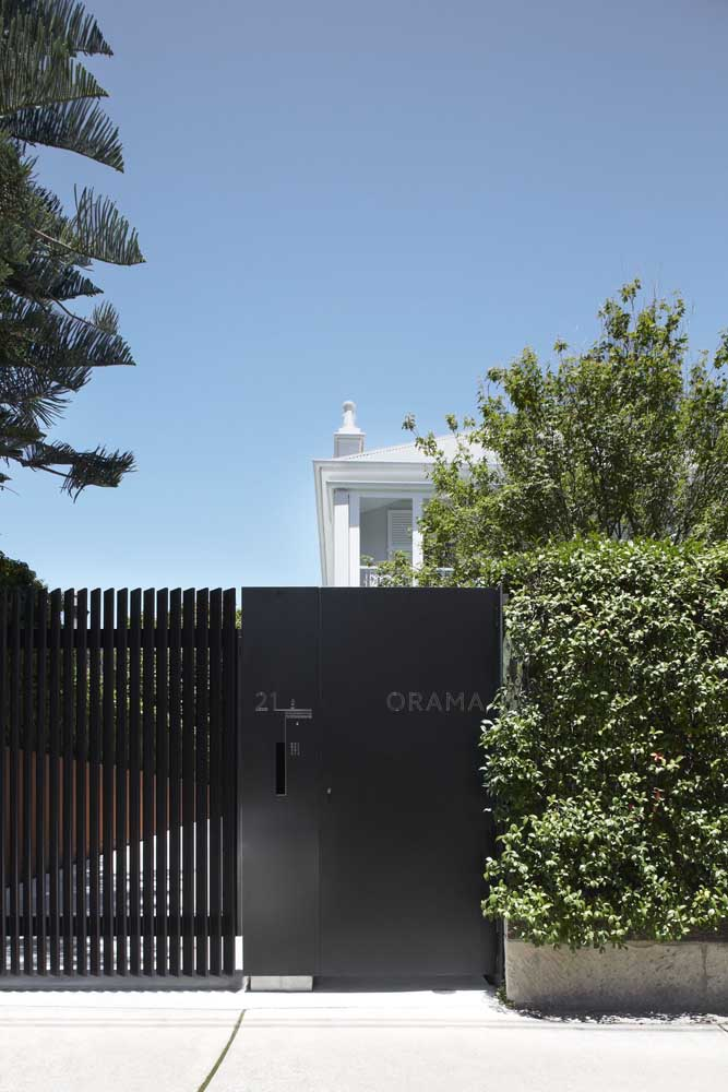 Fachada de muro com portão; ao lado são as plantas que se destacam
