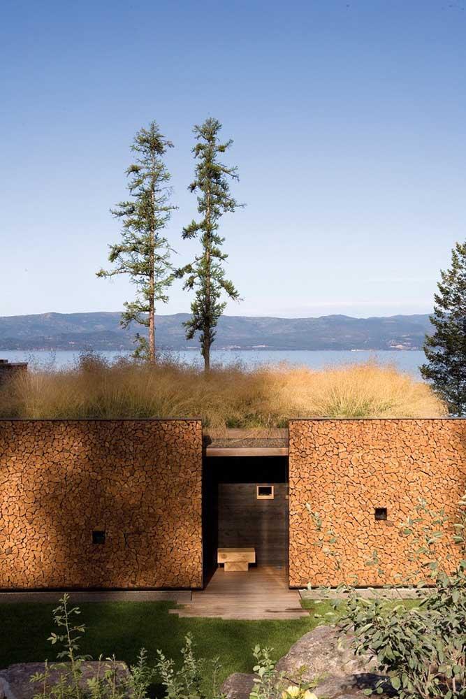 Pequenos pedaços de madeira foram escolhidos para a fachada do muro dessa residência; o resultado final é um mosaico encantador