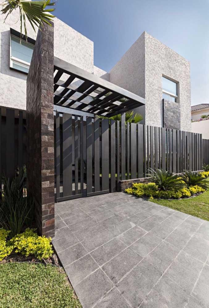 Fachada de muro em placas de ferro alinhadas; o visual vazado permite que o interior da casa seja visualizado por quem está do lado de fora