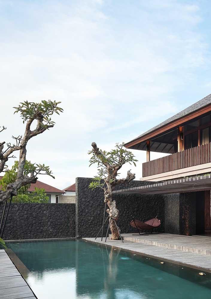 O muro com acabamento em pedras escuras é parte fundamental da estética externa dessa casa