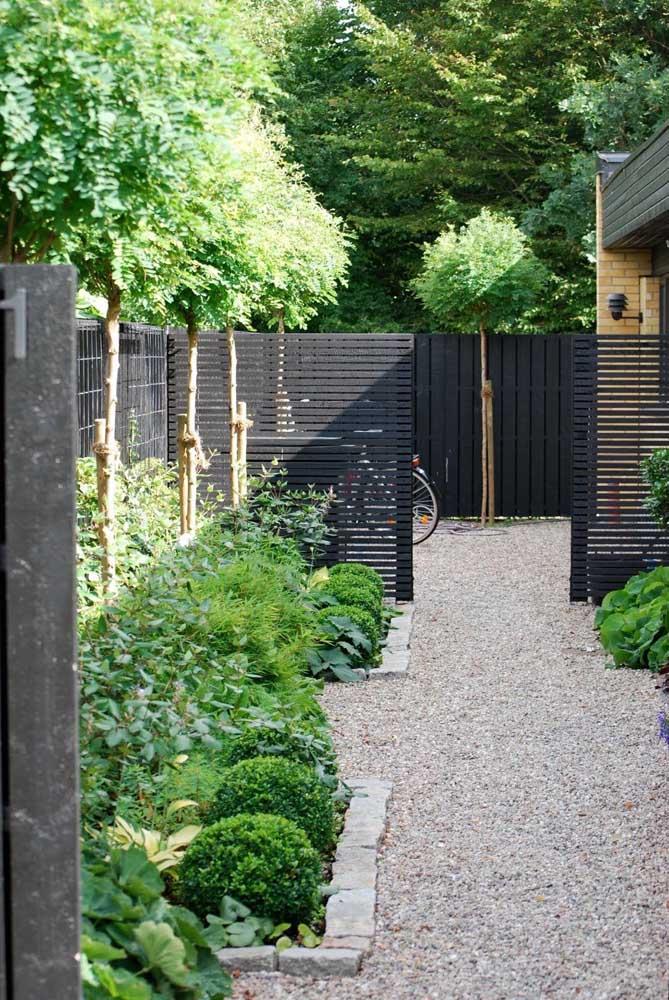 Fachada de muro feita com ripas de madeira pintadas de preto