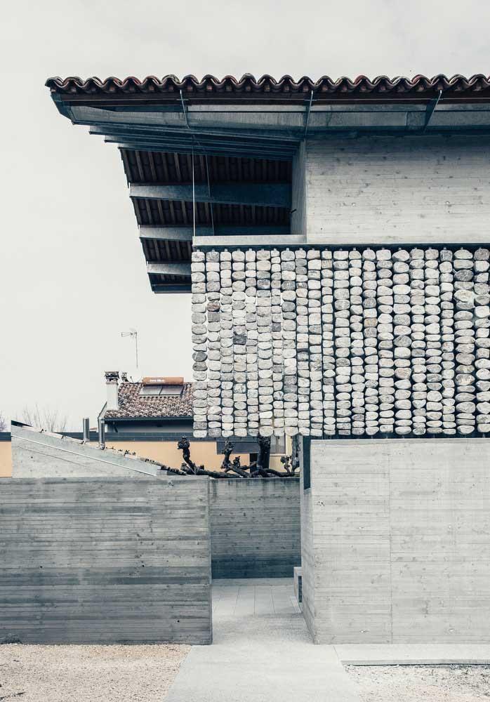 A fachada desta casa uniu como revestimento as pedras, a alvenaria e as placas de madeira, tudo puxando para a mesma tonalidade de cinza