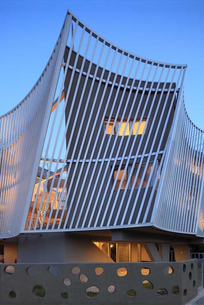 Fachada de muro criativa com ornamentos em ferro e muro baixo em alvenaria com espaços vazados