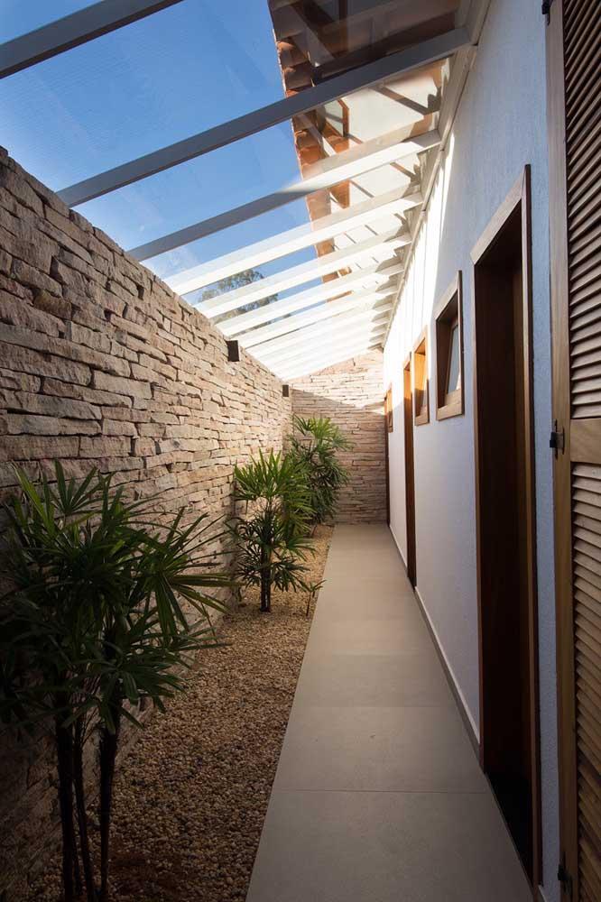 Fachada de muro com pedras naturais para combinar com o pequeno jardim no canteiro da casa
