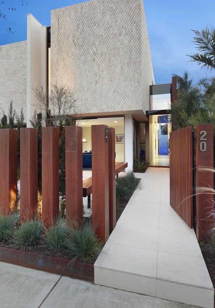 Fachada de muro com madeira em colunas grossas para combinar com o portão no mesmo material