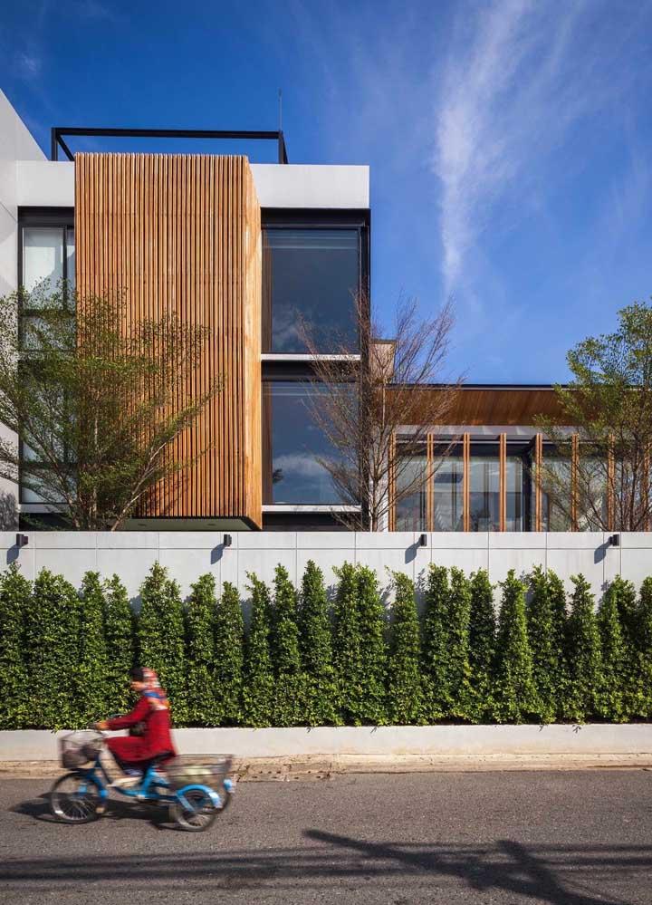 A fachada desta casa contou com dois elementos: o verde das pequenas árvores e a alvenaria