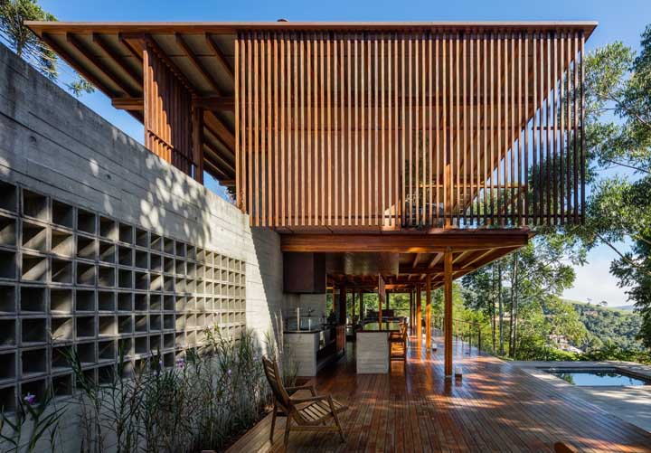 Essa casa contemporânea traz um muro de alvenaria com blocos vazados em contraste com a madeira da fachada