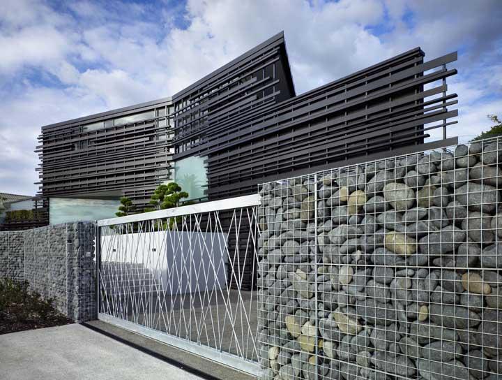 Fachada original formada por gambiões de pedra e portão vazado de metal