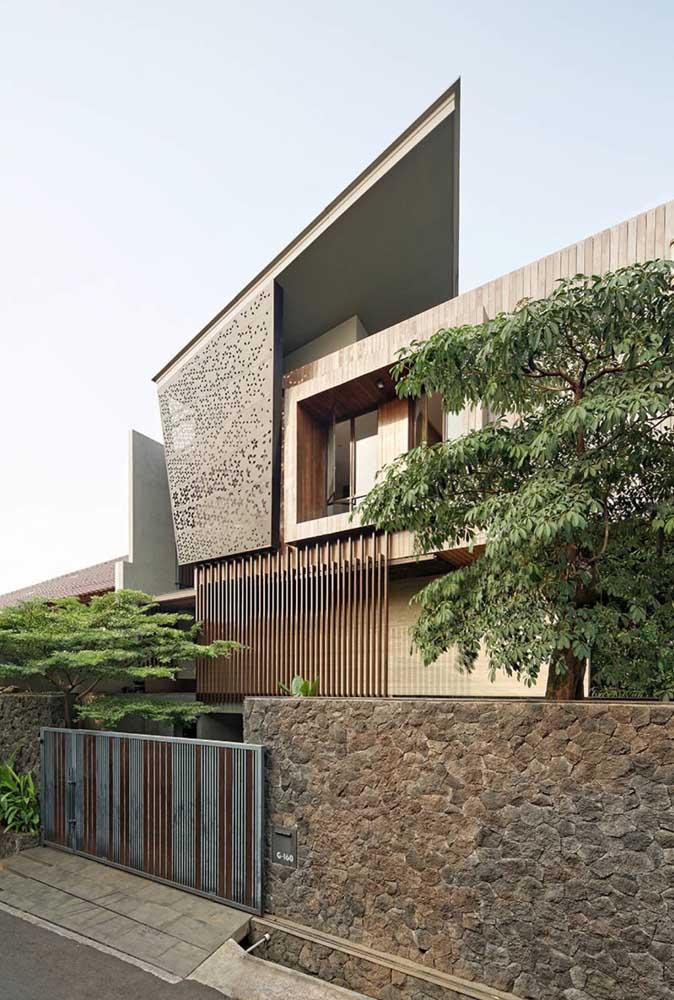 Fachada de muro com portão; o mix entre metal e pedras garantiu modernidade ao projeto