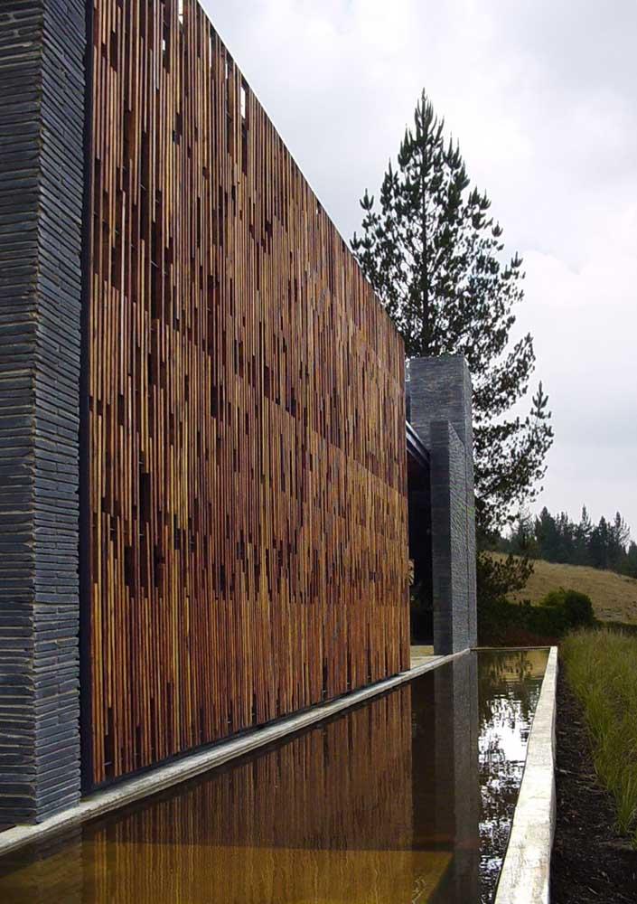 Fachada de muro alto em madeira com detalhes em filetes de pedras ao lado do lago artificial