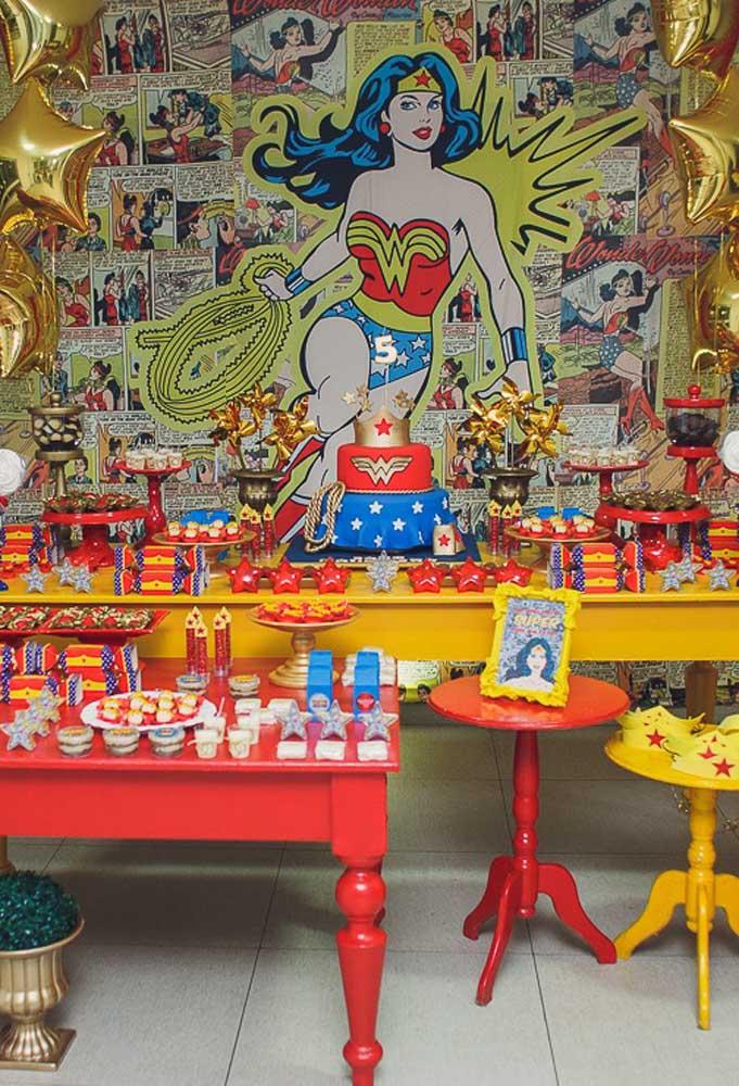 As cores principais da Mulher Maravilha estão presentes tanto no painel quanto na decoração da mesa.