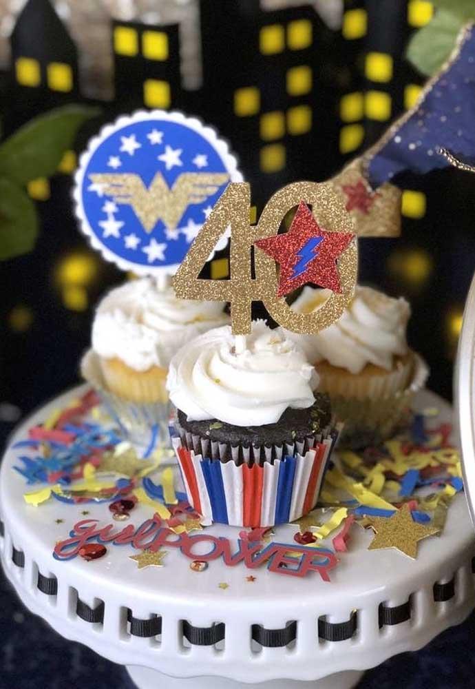 Não sabe como enfeitar o cupcake mulher maravilha? Coloque alguns símbolos mulher maravilha no topo.