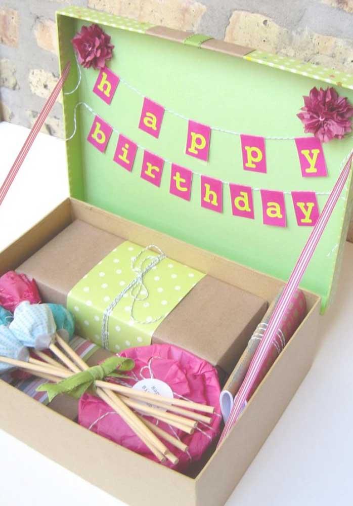 Aproveite todos os espaços da caixa para ajeitar a festa; aqui, a tampa virou painel para as bandeirolas
