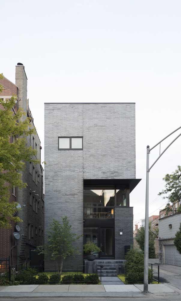 A casa de esquina traz uma frente revestida com cerâmica de tijolinhos cinza