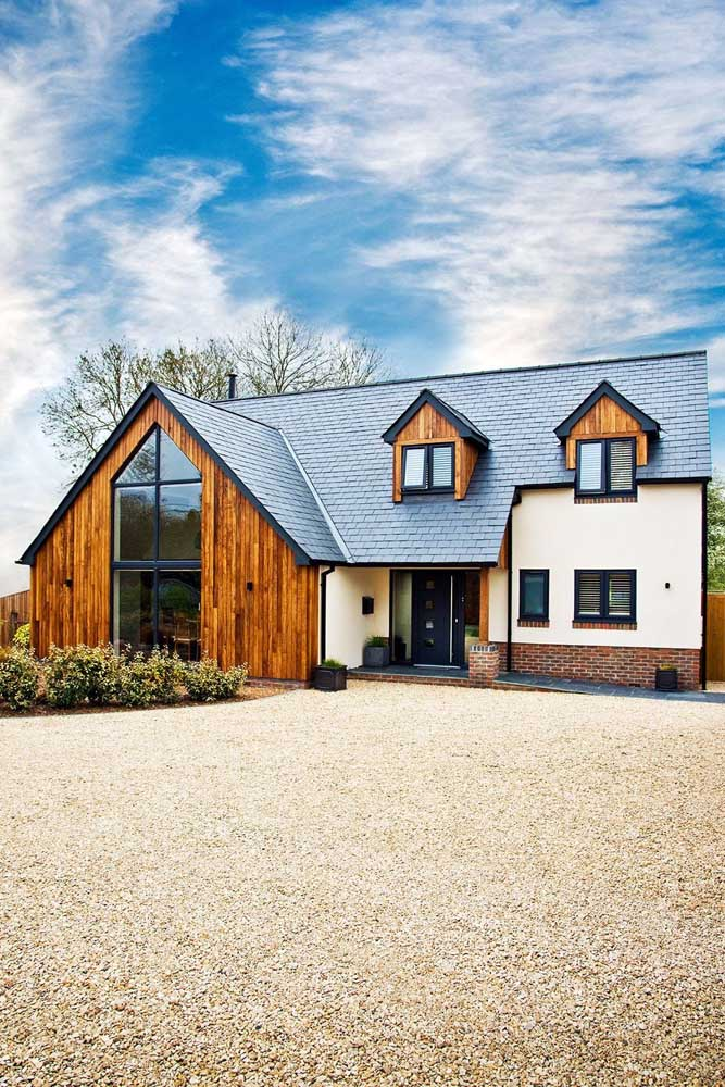 Frente de casa com telhado aparente reforçando a estética rústica do projeto