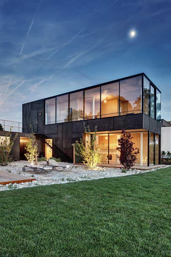 Frente de casa moderna com jardim; o vidro traz leveza ao projeto