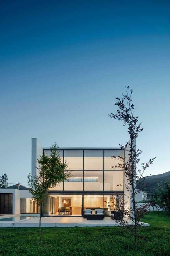 Frente de casa com piscina e jardim; ideal para inspirar projetos de casas maiores