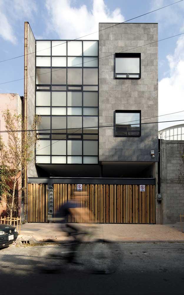 Essa frente de casa moderna ganhou um toque de rusticidade com o muro e portão de madeira