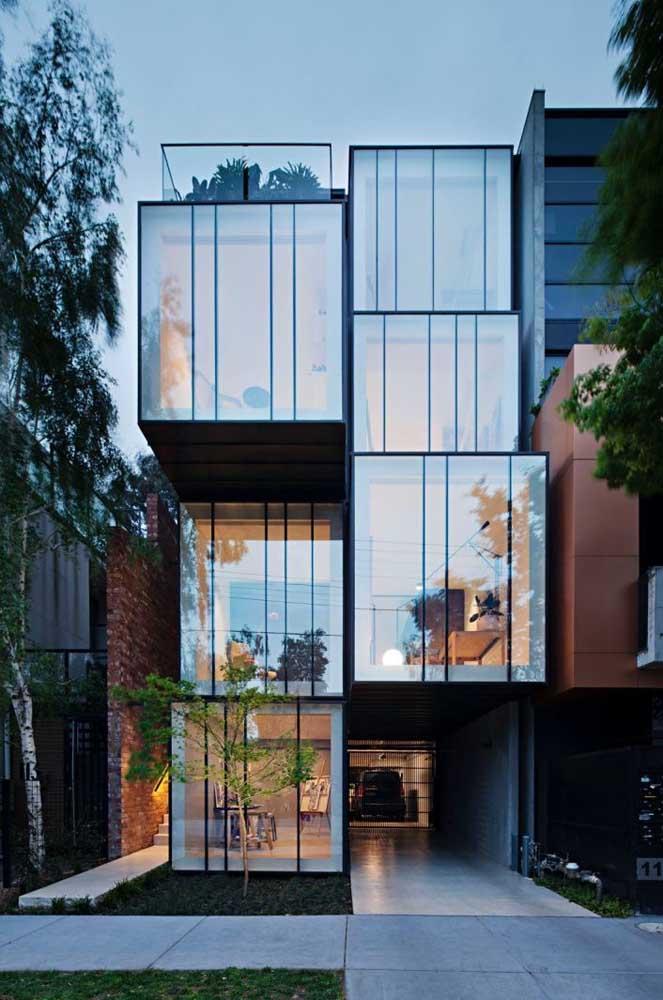 A frente dessa outra casa é toda revestida com vidros, uma inspiração leve e moderna para o projeto