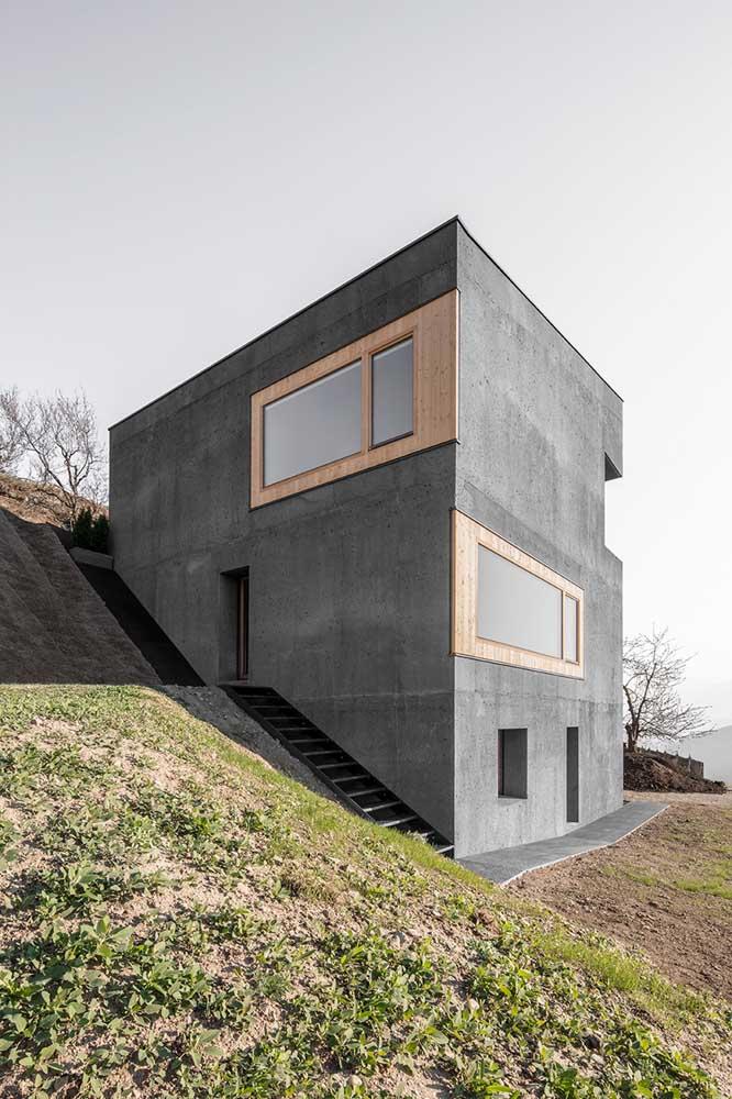 O terreno em declive revela uma casa moderna com revestimento de cimento queimado