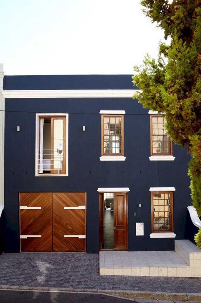 O tom de azul escuro trouxe elegância para a frente dessa casa; repare que o uso da madeira casou perfeitamente com a tonalidade escolhida