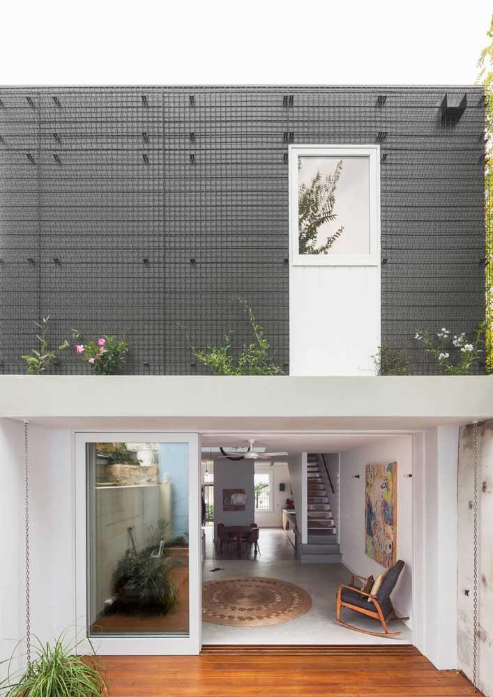 Já aqui, o material usado para diferenciar a frente da casa é a treliça metálica
