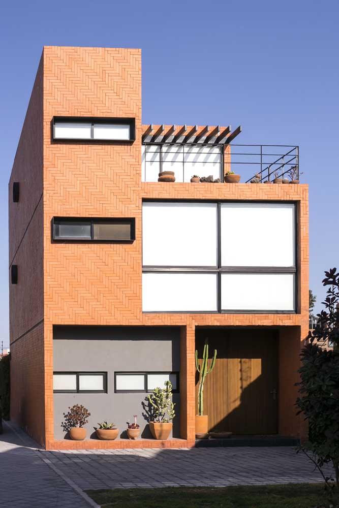 Frente de casa com revestimento cerâmico de tijolinhos; repare na harmonia entre o moderno e o rústico