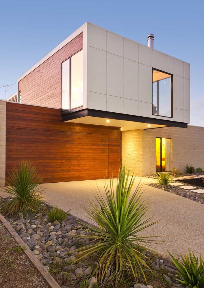 Frente de casa com muro de pedra e portão de madeira; destaque para o uso da iluminação indireta valorizando o projeto
