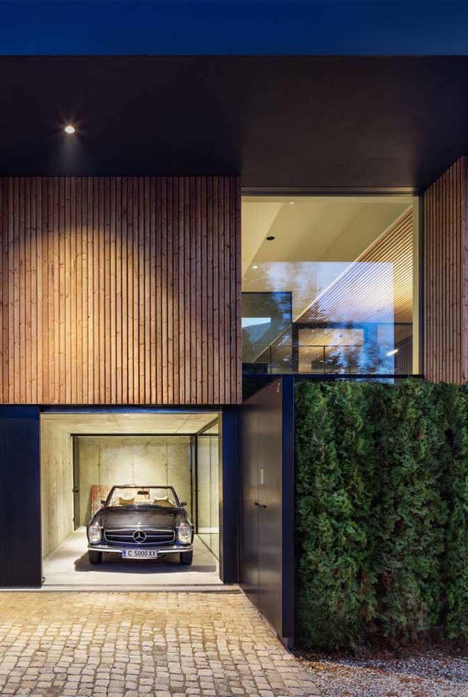 Frente de casa moderna com acabamento em pintura azul, painel de madeira, vidro e muro verde: uma junção ideal de elementos
