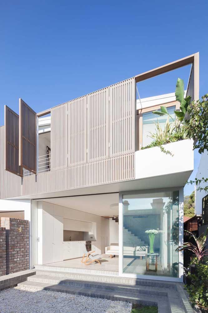 Frente de casa moderna com cores neutras e painel de madeira