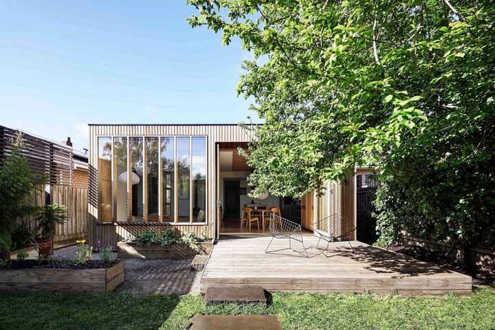 Essa frente de casa simples contou com ripas de madeira e plantas