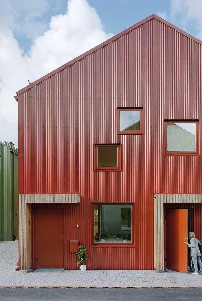 O tom terroso da fachada remete a uma estética rústica, mas a presença do metal logo rebate essa ideia