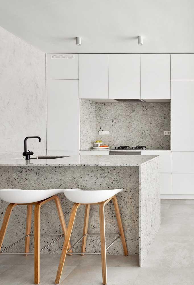 Bancada de cozinha americana simples com granito branco; repare que a pedra também foi aplicada na parede do fogão