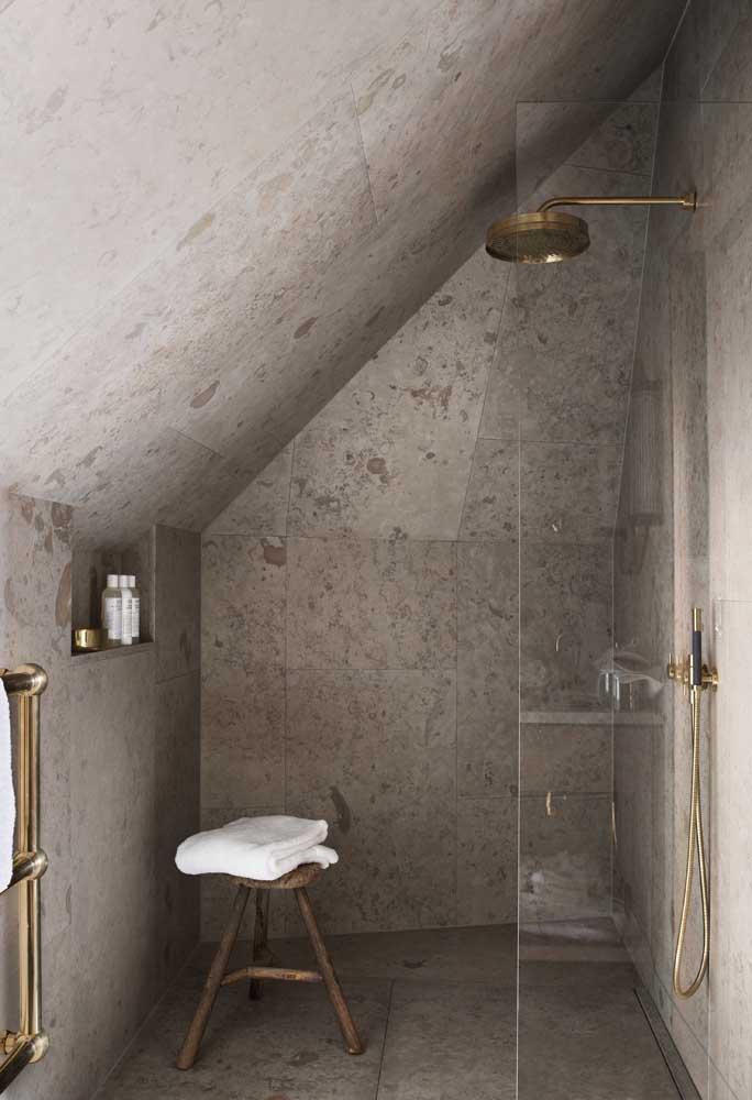 Banheiro em estilo contemporâneo com revestimento em granito branco e peças em dourado para completar a proposta