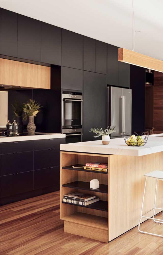A cozinha moderna ficou perfeita com a pequena bancada em granito branco contracenando com a madeira e os armários em preto