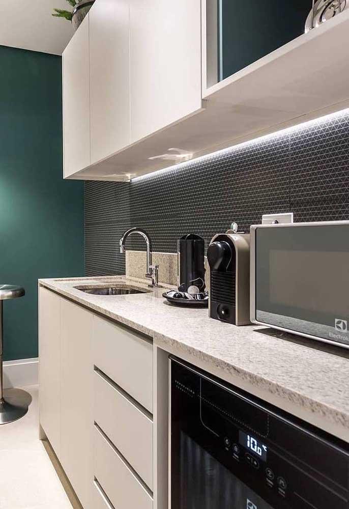 Para combinar com as paredes em tons de verde e com revestimento em 3D, a opção foi usar o granito branco na bancada