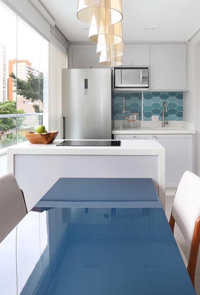 A pequena cozinha do apartamento fez uma combinação linda entre o granito branco e o tons de azul presentes na mesa e no revestimento da parede