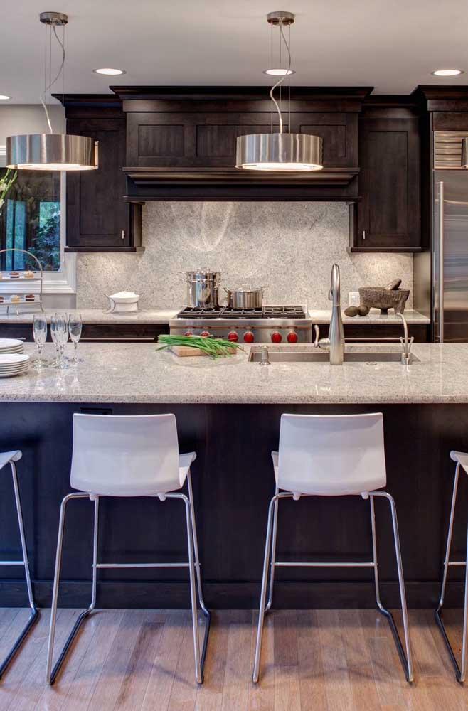Granito branco para o balcão e parede da cozinha; repare que os tons escuros presentes no restante da decoração formam um bonito jogo de contrastes