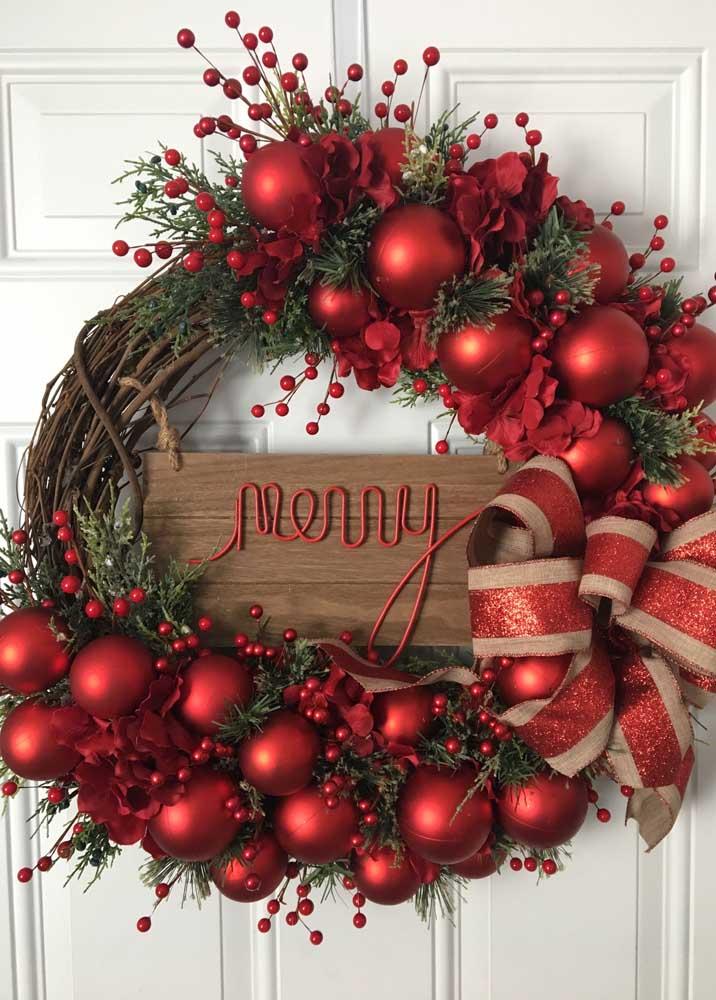 Essa outra guirlanda traz o vermelho típico do natal para enfeitar a guirlanda com base de galhos de árvore