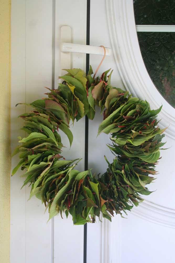 Chame as crianças para recolher folhas de árvore e, na volta, montem uma guirlanda como essa; olha como é diferente e criativa!