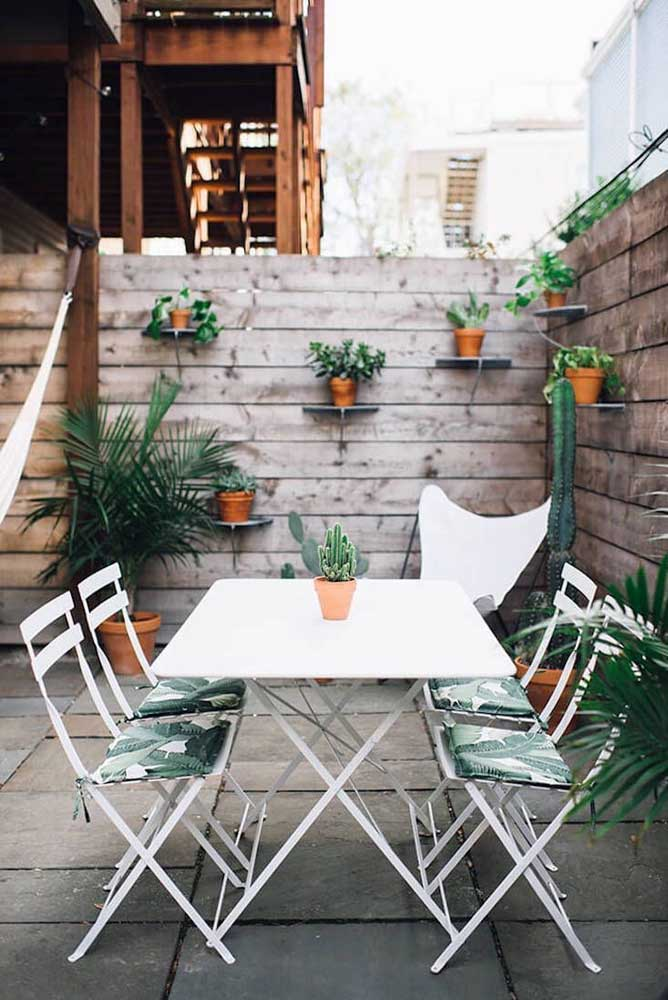 Nessa casa, a parede revestida com madeira é a base de sustentação para o jardim simples vertical; alguns poucos vasos no chão foram usados para completar o visual externo