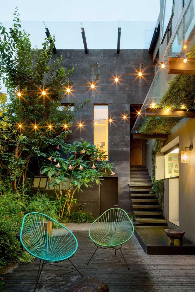 O varal de lâmpadas dá um toque todo especial ao jardim simples da casa