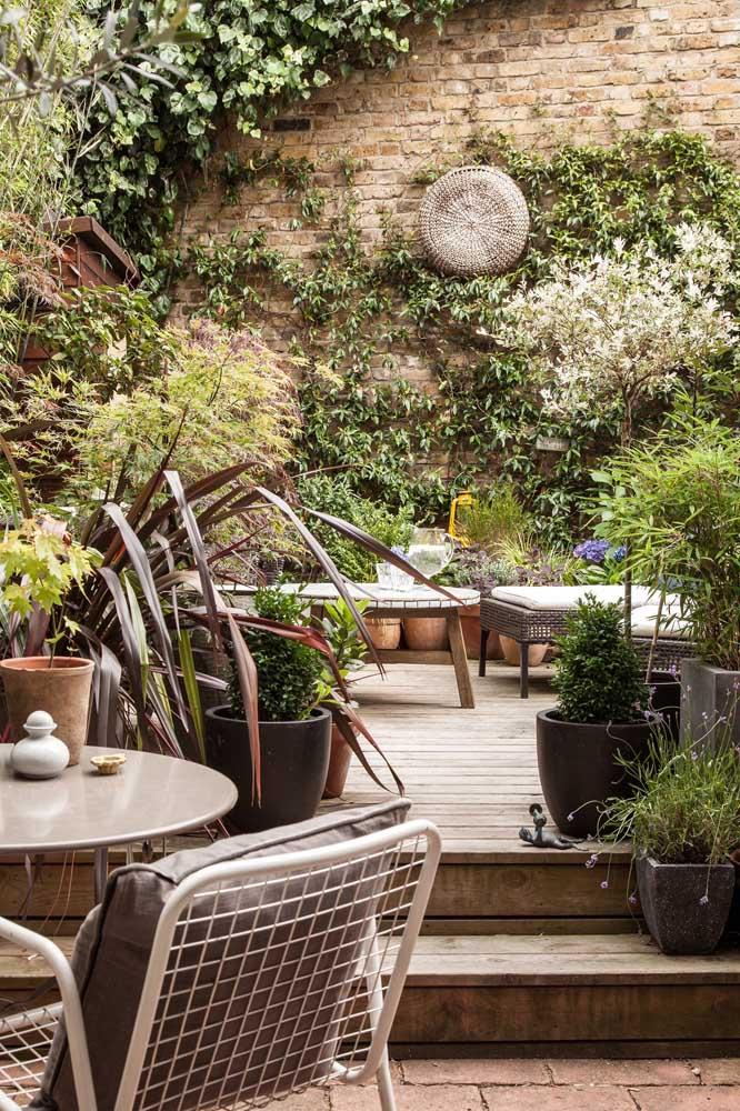 Já nesse espaço externo rústico, a parede de tijolinhos ganhou a companhia de uma planta trepadeira, dando mais profundidade ao cenário verde criado pelos vasos