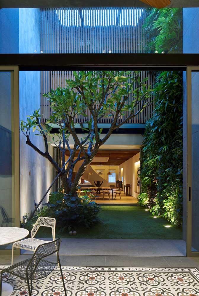 A ligação entre as duas partes da casa é feita através da passagem pelo jardim simples, de gramado impecável