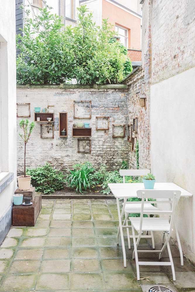 Jardim simples, pequeno e com um toque rústico super charmoso graças à parede de tijolinhos e as antigas molduras na parede