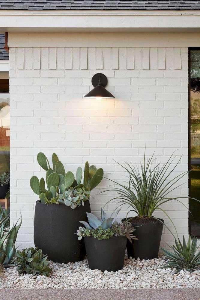 Aqui, o trio de vasos em tamanhos diferentes repousa sobre o chão de pequenas pedrinhas; para completar o visual charmoso do lugar, uma luminária de parede