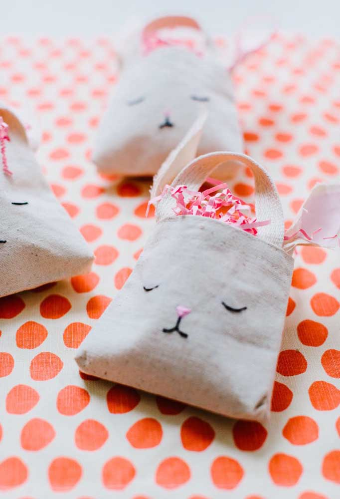 Você pode usar tecido de algodão cru para fazer sacolinhas. Para personalizar, borde a carinha do coelho na frente de cada sacola.
